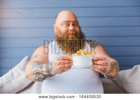 I am ready for diet. Happy fat man is showing bowl of cornflakes to camera. He is sitting on sofa and smiling. Focus on healthy food