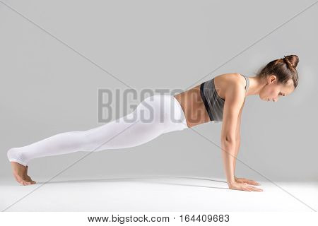 Young attractive woman practicing yoga, in Push ups or press ups exercise, phalankasana, Plank pose, working out wearing sportswear, white pants, indoor full length, isolated grey studio background