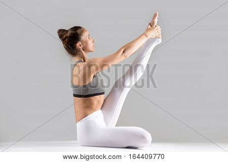Young attractive woman practicing yoga, sitting in Heron exercise, Krounchasana pose, working out wearing sportswear, white pants, bra, indoor full length, isolated against grey studio background