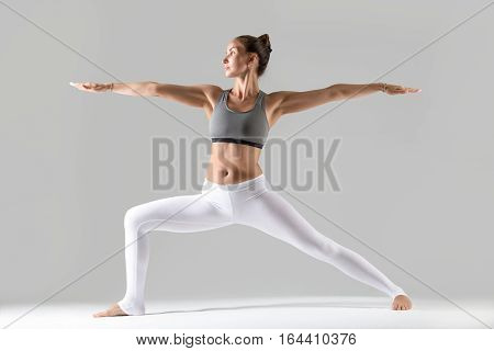 Young attractive woman practicing yoga, standing in Warrior Two exercise, Virabhadrasana II pose, working out wearing sportswear, indoor full length, isolated, grey studio background