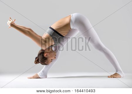 Young attractive woman practicing yoga, standing in One Sided Fold, Pyramid, exercise, Parsvottanasana pose, working out wearing sportswear, indoor full length, isolated against grey studio background