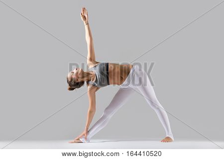 Young attractive woman practicing yoga, standing in extended triangle exercise, Utthita Trikonasana pose, working out wearing sportswear, indoor full length, isolated against grey studio background