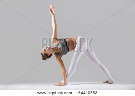 Young attractive woman practicing yoga, standing in Revolved Triangle exercise, Parivrrta Trikonasana pose, working out wearing sportswear, indoor full length, isolated against grey studio background