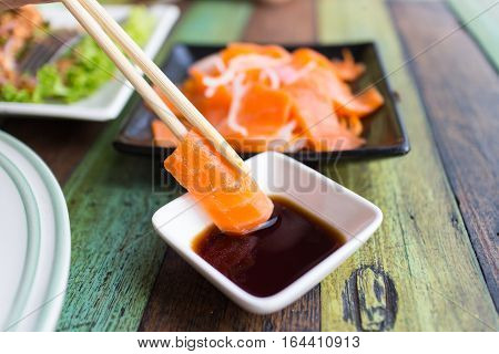 Sashimi Salmon chopsticks dipping sauce on Dining table