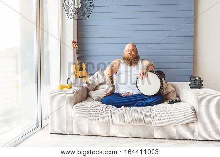 Joyful fat man is holding drum with confidence. He is sitting on sofa with relaxation near small guitar