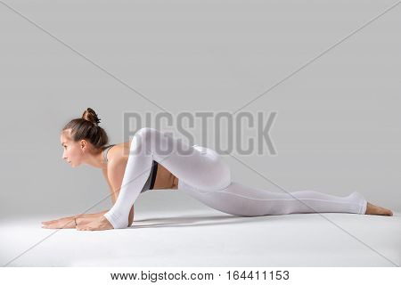 Young attractive woman practicing yoga, stretching in Lizard exercise, Utthan Pristhasana pose, working out wearing sportswear, white pants, top, indoor full length, isolated, grey studio background