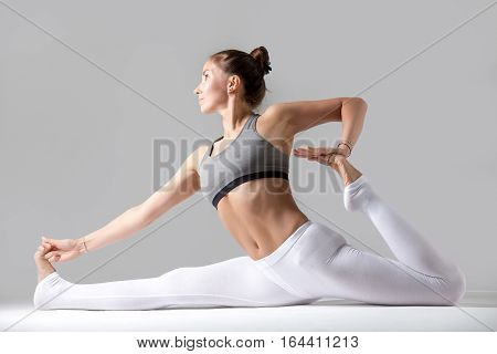 Young attractive woman practicing yoga, sitting in Monkey God, Splits exercise, Hanumanasana pose, working out wearing sportswear, white pants, top, indoor full length, against grey studio background