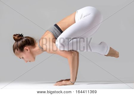 Young attractive woman practicing yoga, standing in Crane exercise, Bakasana pose, working out wearing sportswear, white pants, gray top, indoor full length, isolated against grey studio background