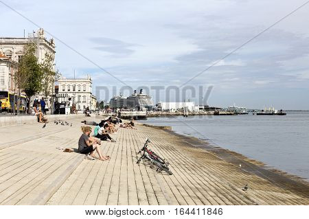 LISBON, PORTUGAL - September 27, 2016: People and the Tagus River beach and niverside promenade called Ribeira das Naus Avenue with a cruise ship docked in Lisbon Portugal