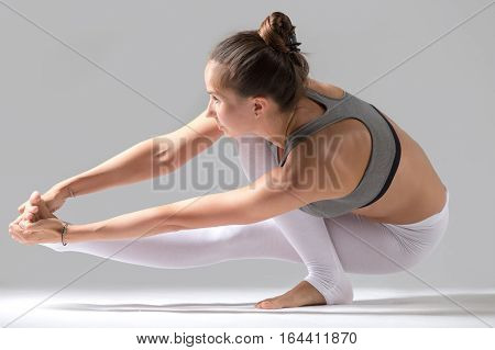 Young attractive model girl practicing yoga, doing Squat Balance with twisting variation of Extended Hand to Big Toe pose, working out indoors, full length, isolated, grey studio background