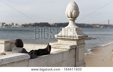 LISBON, PORTUGAL - September 27, 2016: Person enjoying the good weather by the Tagus River in downtown Lisbon Portugal