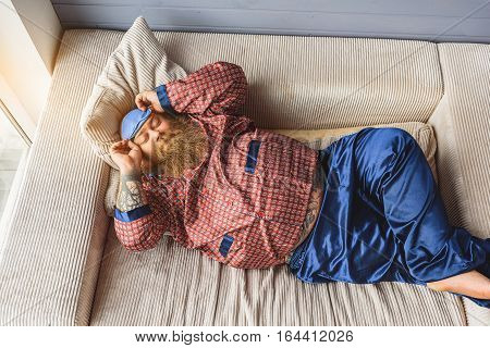 Happy male fatso is relaxing on sofa in pajamas. He is touching mask while sleeping. His eyes are closed with pleasure