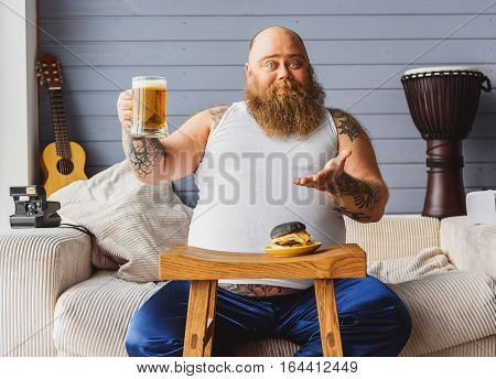 Sit down and drink with me. Carefree fat man is holding glass and gesturing with invitation. He is sitting on sofa with large belly