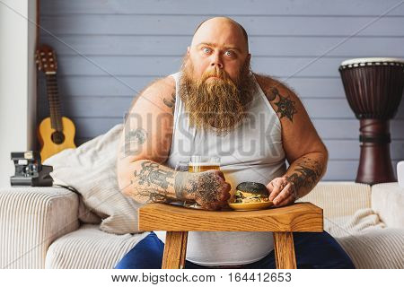 Hungry fat man is holding glass of beer and sandwich. He is sitting on sofa and looking at camera with greed