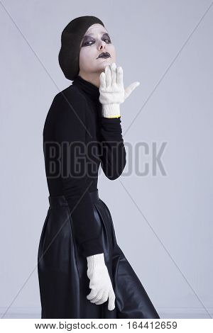 Young woman mime on a background of gray wall