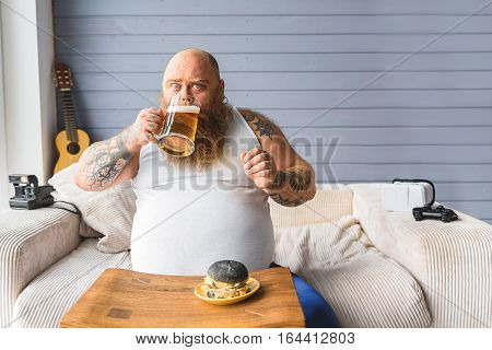 Scared fat guy is drinking beer and looking at camera with fear. He is sitting on sofa near junk food on table