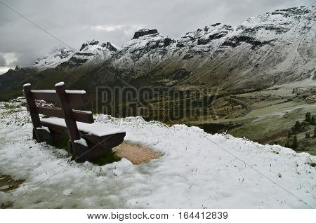 Passo Pordoi: bench covered by the first snow of the season on the Dolomiti mountains