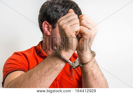 Arrested man in handcuffs hidden his face in front of camera