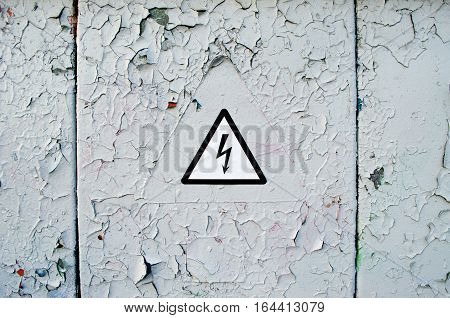 Caution. High voltage. Warning of the danger sign on a metal wall