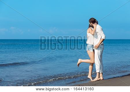 romance on vacation: couple in love on the beach flirting.