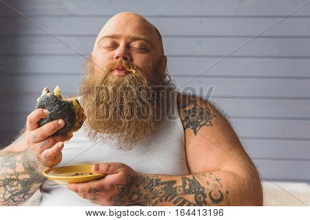 Greedy fat man is eating unhealthy burger with enjoyment. His eyes are closed and sauce on his beard