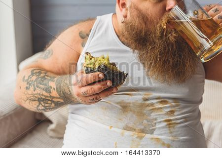 Fat drunk man is drinking alcohol beverage with desire. He is sitting and holding bitten hamburger. His shirt is dirty