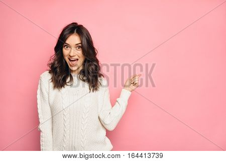 funny surprised girl showing empty copy space with her finger over pink color background. Happy young brunette woman pointing, looking at camera