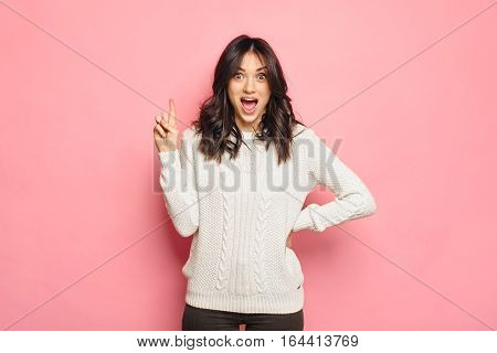 shocked brunette Woman with surprised Facial Expression pointing her finger up against Pink Background