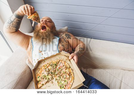 Male glutton is holding piece of pizza under his open mouth. He is lying on couch with laziness