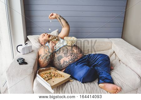 Hungry male heavy eater is pouring popcorn into his mouth with enjoyment. He is lying on couch with laziness near box of pizza