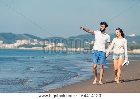 Couple walking on beach. Young happy interracial couple walking on beach smiling holding around each other