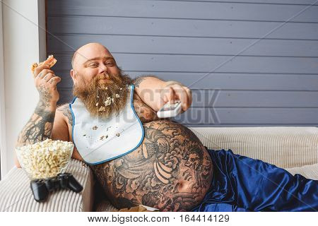 Pizza and television are my friends. Happy fat man is holding remote control and smiling. He is lying on couch near junk food
