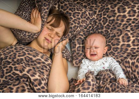 Tired mother can't to sleep because her baby won't stop crying