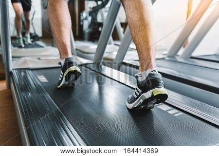 Focus on legs of guy. He is running at treadmill