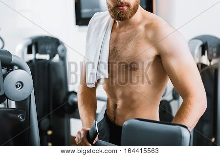 Half-naked muscled sporty guy is standing nearby power training apparatus. He holding mobile