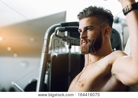 Assured strong bearded sportsman is sitting at power training apparatus, he looking ahead