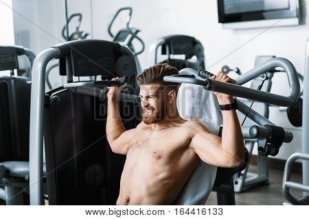 Strong sportsman is sitting at power training apparatus. He hardly taking exercise