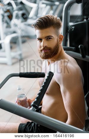 Smiling muscled man is sitting at apparatus. He looking at camera and holding bottle of water