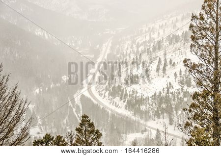 Looking down from the top of a mountain pass to the road below. Snow was blowing making it look almost foggy.