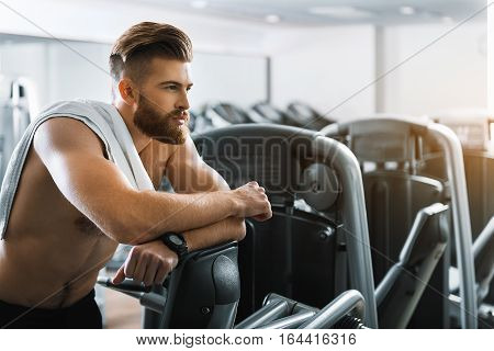 Confident powerful bearded sportsman is standing and leaning on power training apparatus. He looking ahead