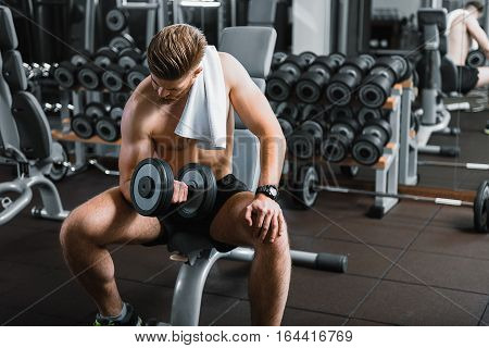 Strong muscled man is sitting at power training apparatus. He lifting dumbbells