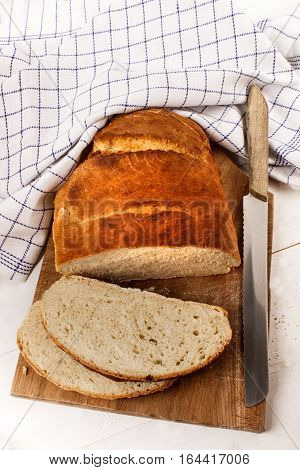 sliced warm bread loaf on a wooden board with knife