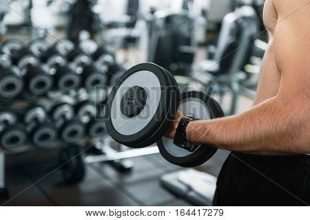 Powerful confident sportsman is standing and taking heavy dumbbells