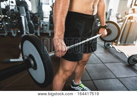 Muscled half-naked man is standing at gym. He holding heavy barbell