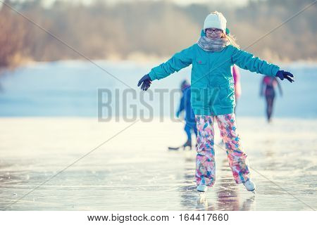 Ice skating. Young girl is skating on a natural frozen lake.