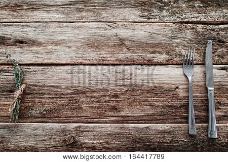 Rustic wooden table with knife and fork free space. Top view on grunge rural background with cutlery and herbs, background for meal advertisement or restaurant menu