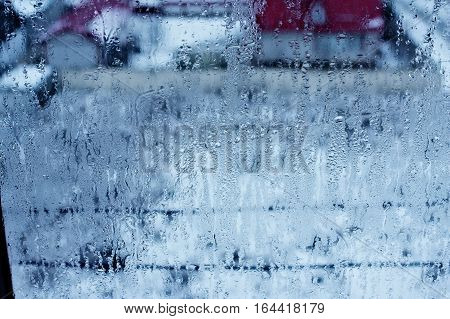 Window glass with condensation, strong, high humidity in the room, large water droplets flow down the , cold tone, natural drops