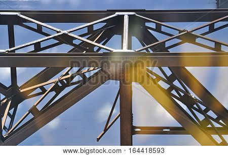 Metal structure with x and blue background with orange light reflection effect