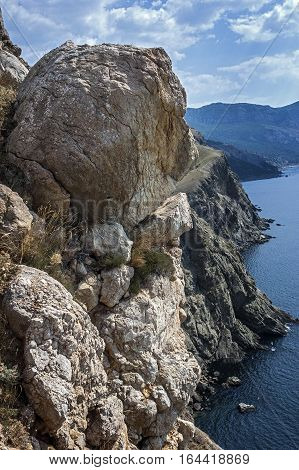 Russia Crimea. Rocks which snap into the sea near Balaklava. Hot Crimean sun-scorched grass rare green bushes mozhevelnik. Huge boulders miraculously hold on a slope.
