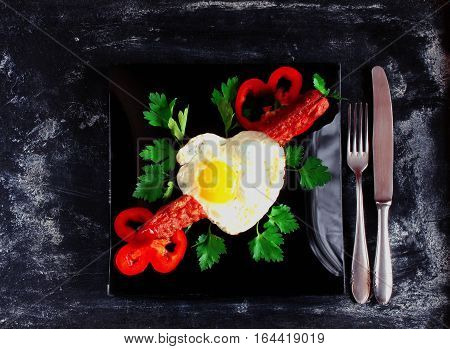 scrambled eggs shape heart fried sausage parsley red pepper slices black plate knife and fork on dark surface